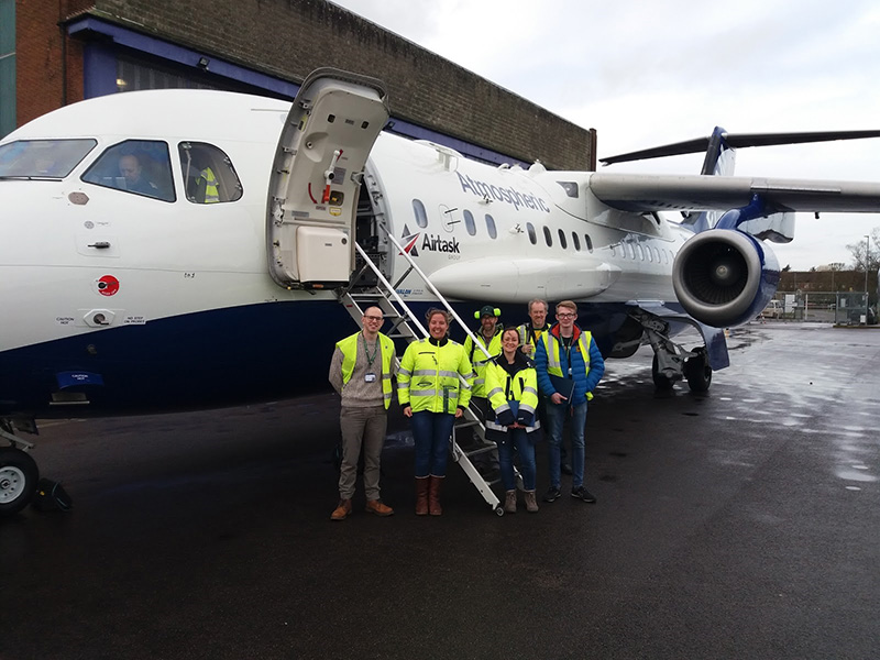 6 people wearing hi-vis jackets, stood the the FAAM research aircraft outside of the aircraft hangar