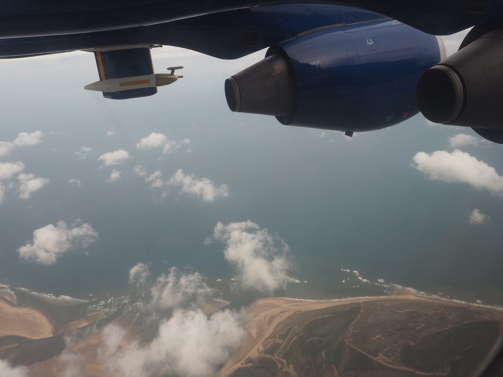 Blue sea below patchy white clouds, viewed from on board the FAAM aircraft